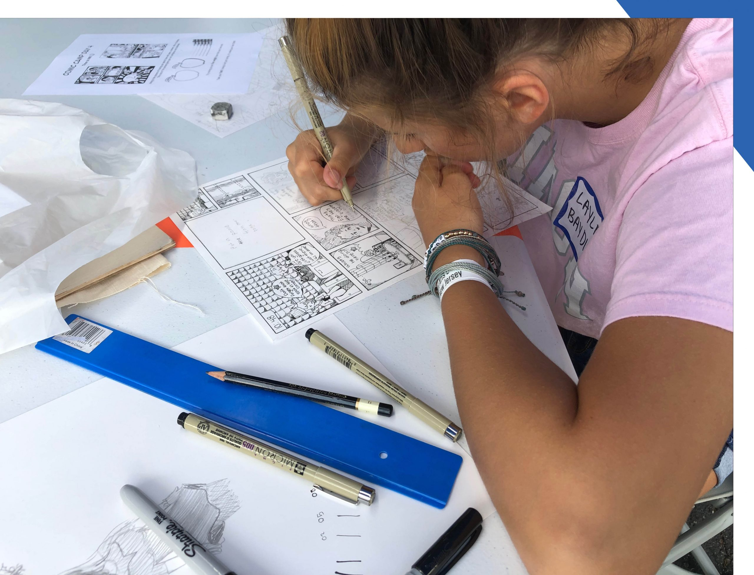Child camper drawing a sequential art project.