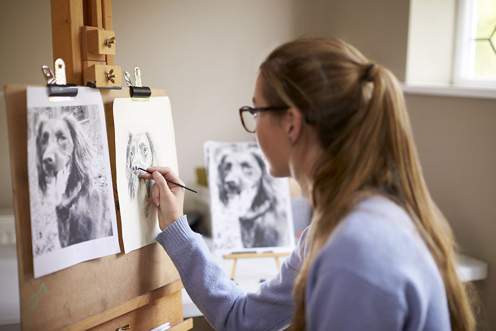 Woman drawing from a picture of a dog