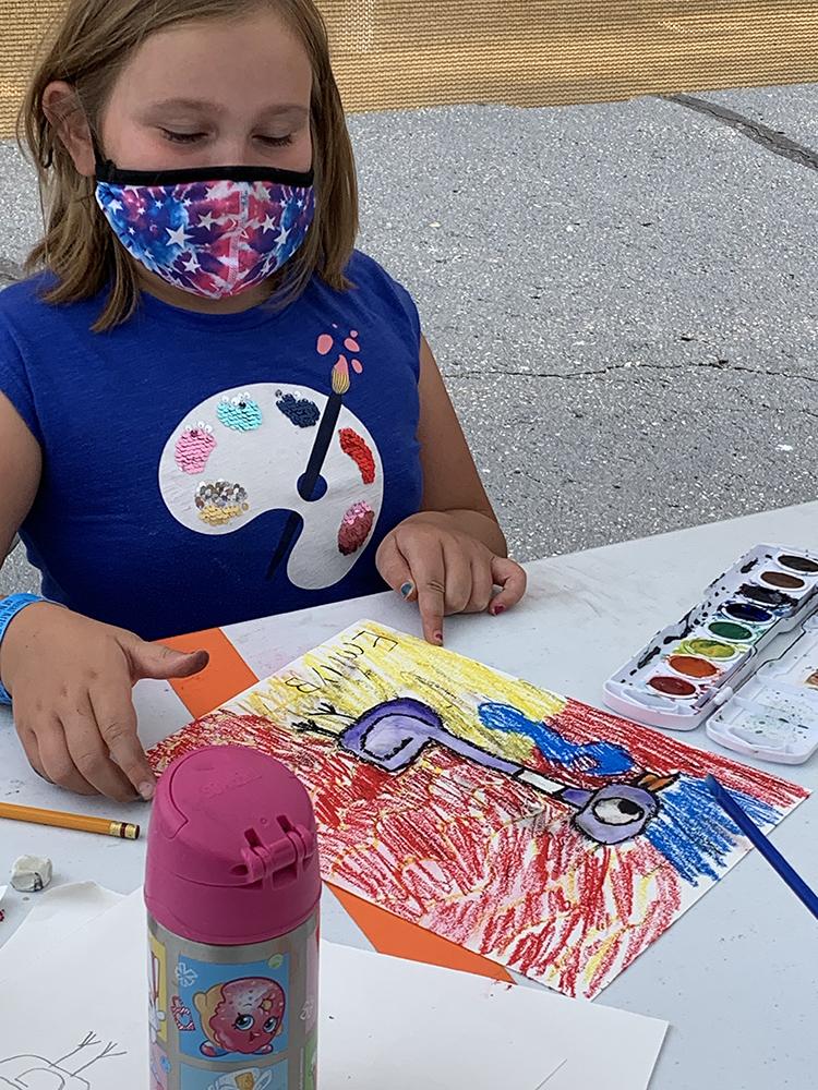 Masked child camper making art